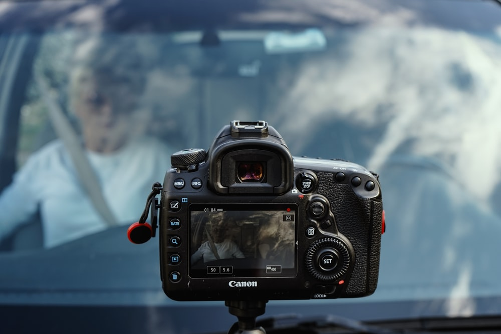 black Canon camera taking photo of man inside vehicle