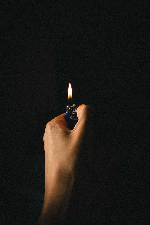 person lighting lighter on black background