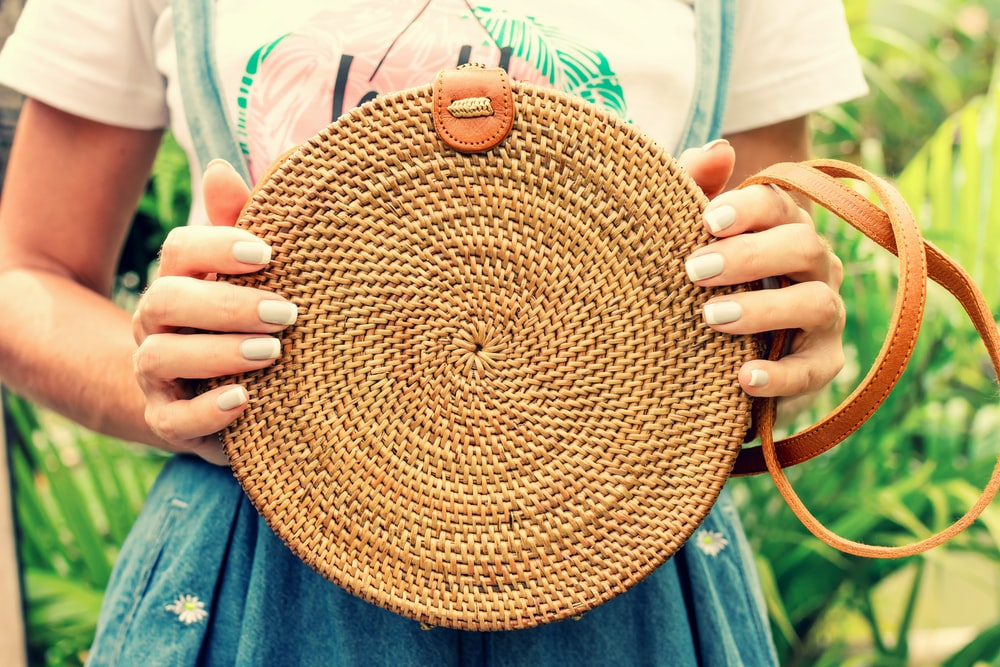 woman holding brown wicker crossbody bag
