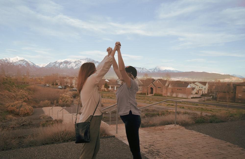 women railing both arms