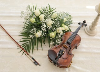 brown violin with bow and flowers bouqet
