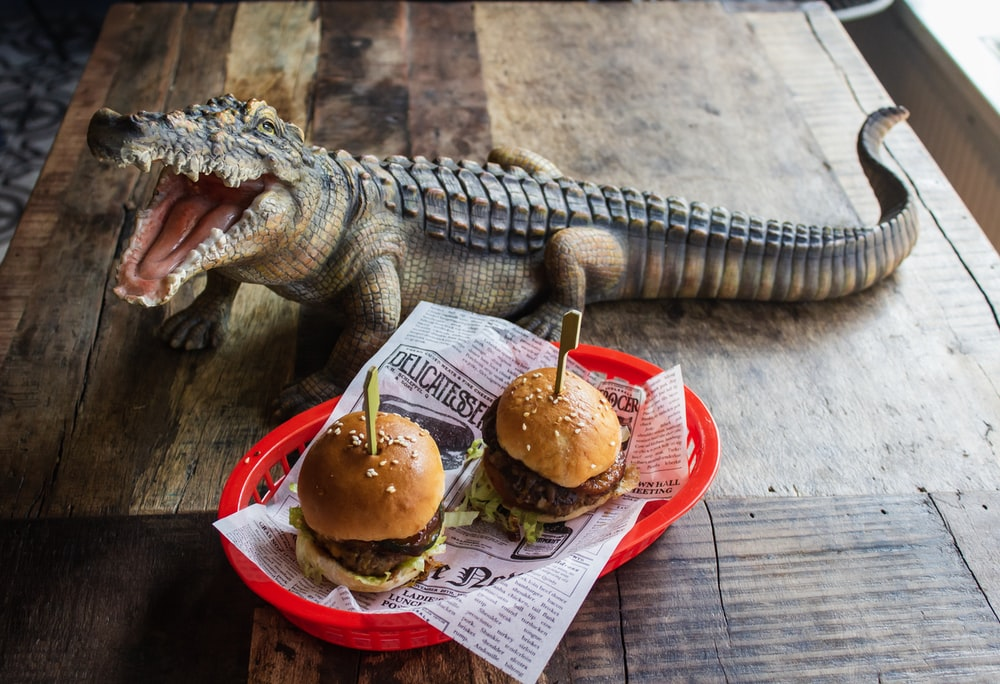 two sliders on plate beside crocodile statuette