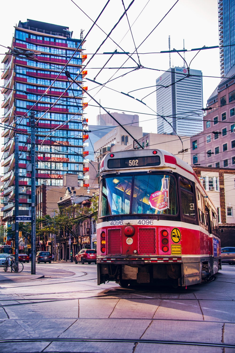 red city tram near blue glass building during daytime