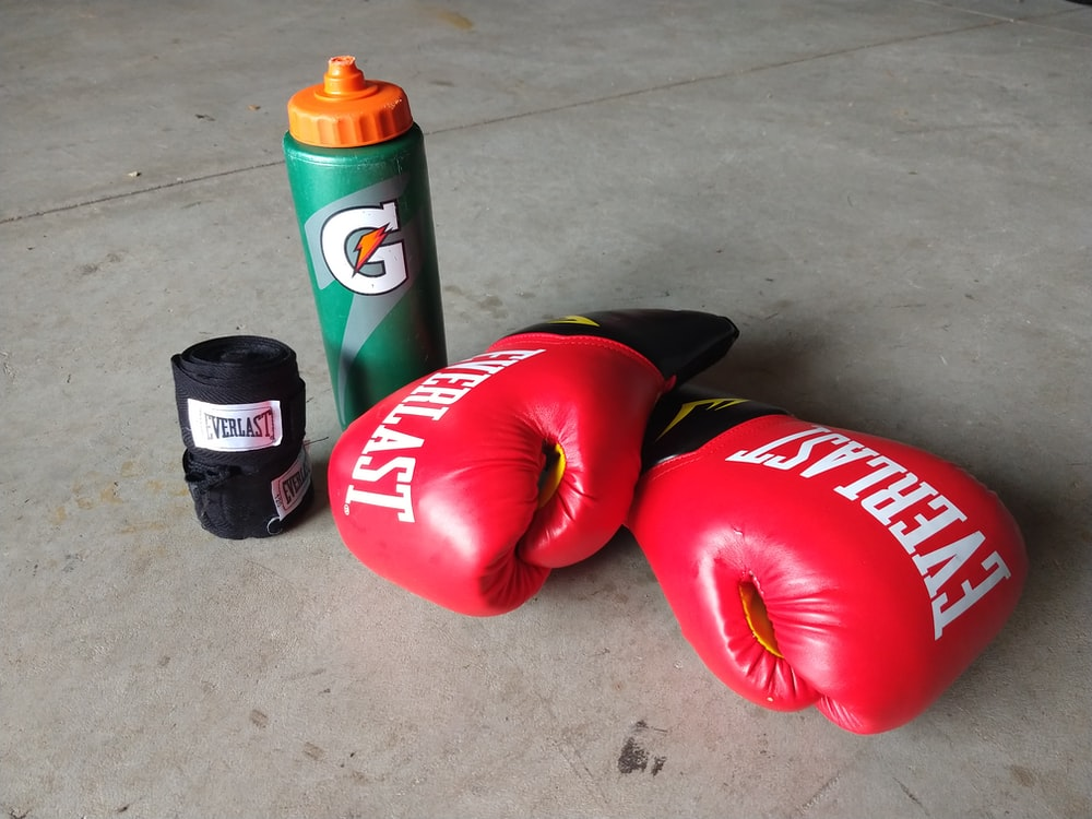 pair of red Everlast boxing gloves beside Gatorade bottle