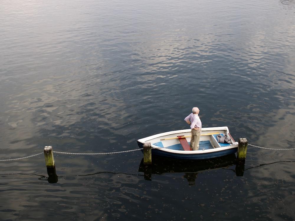 man in white long-sleeved shirt standing on white jon boat during daytime