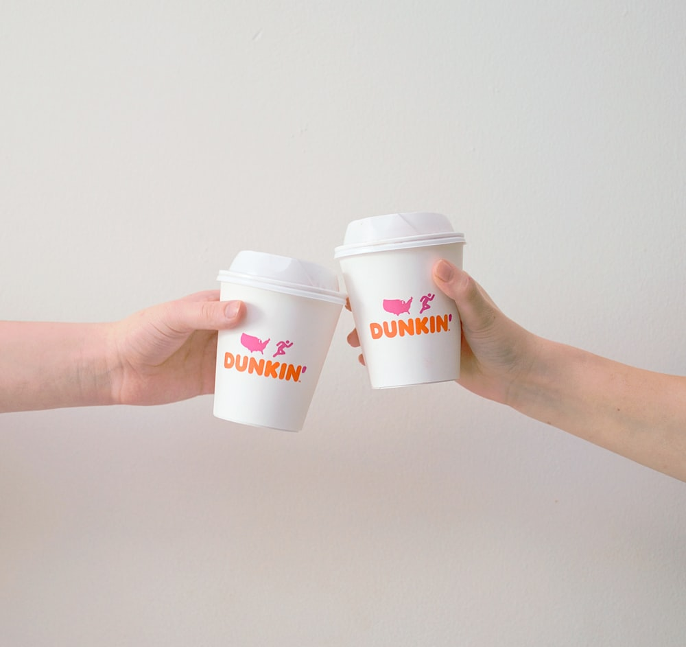 two people with white Dunkin' Donuts paper cups