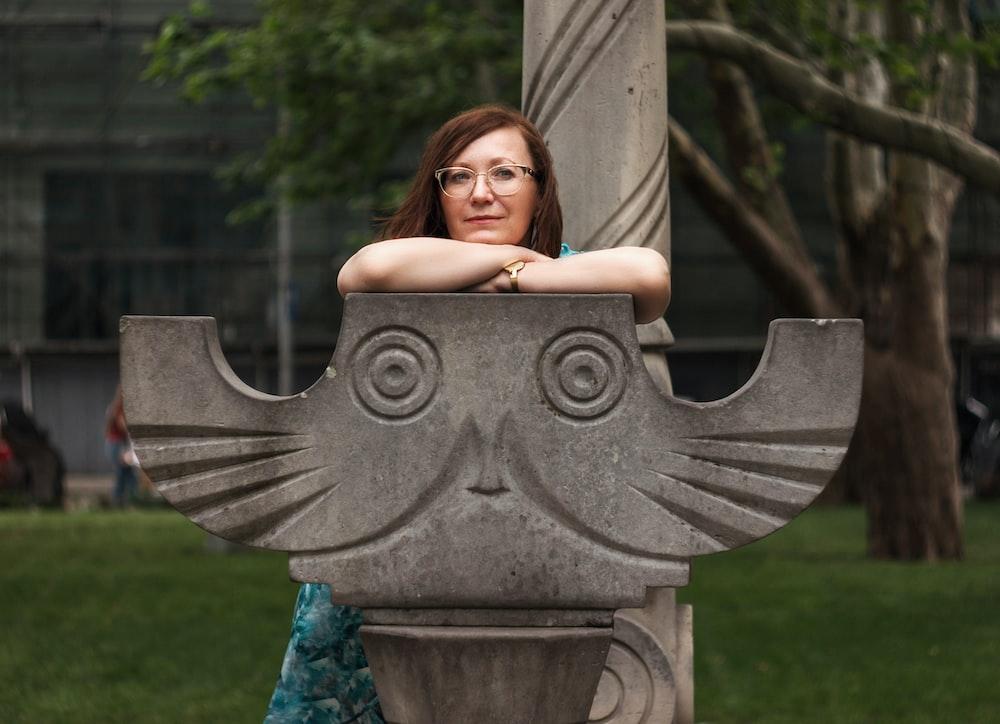 woman sitting on concrete owl seat