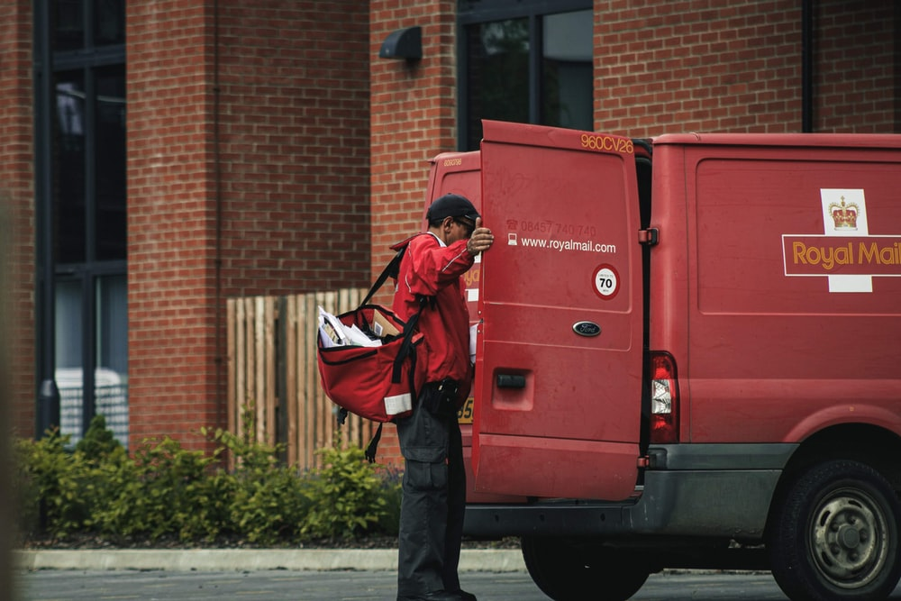 man standing near red van