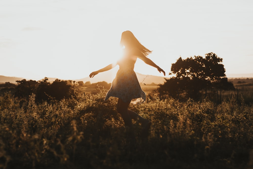 silhouette of woman dancing in the middle of grass field