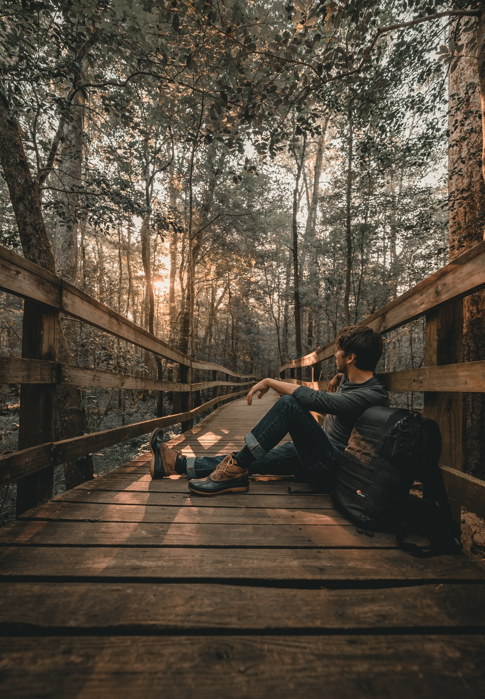 man leaning on bridge
