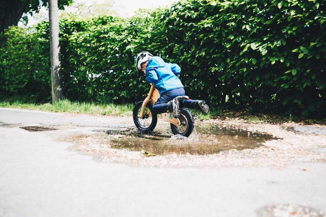 Young boy with training bike balance bike rides through the puddle. Made with Canon 5d Mark III and loved analog lens, Helios 44M 2.0 / 58mm (Year: 1977)