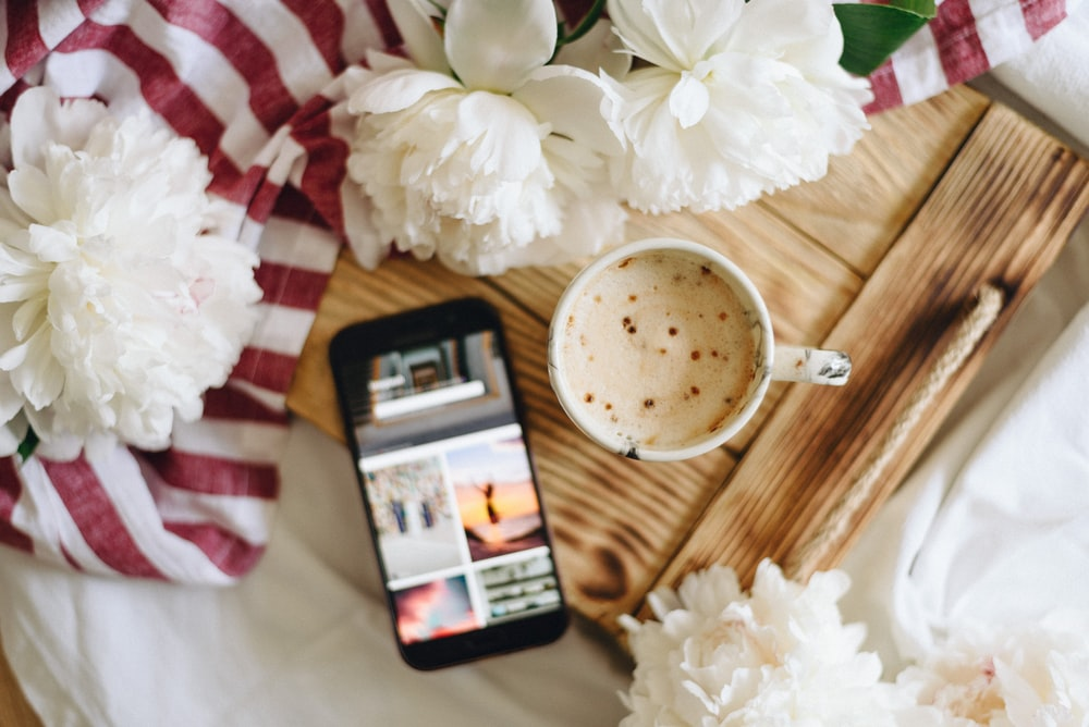 flat lay photography of mug of drink and black Android smartphone