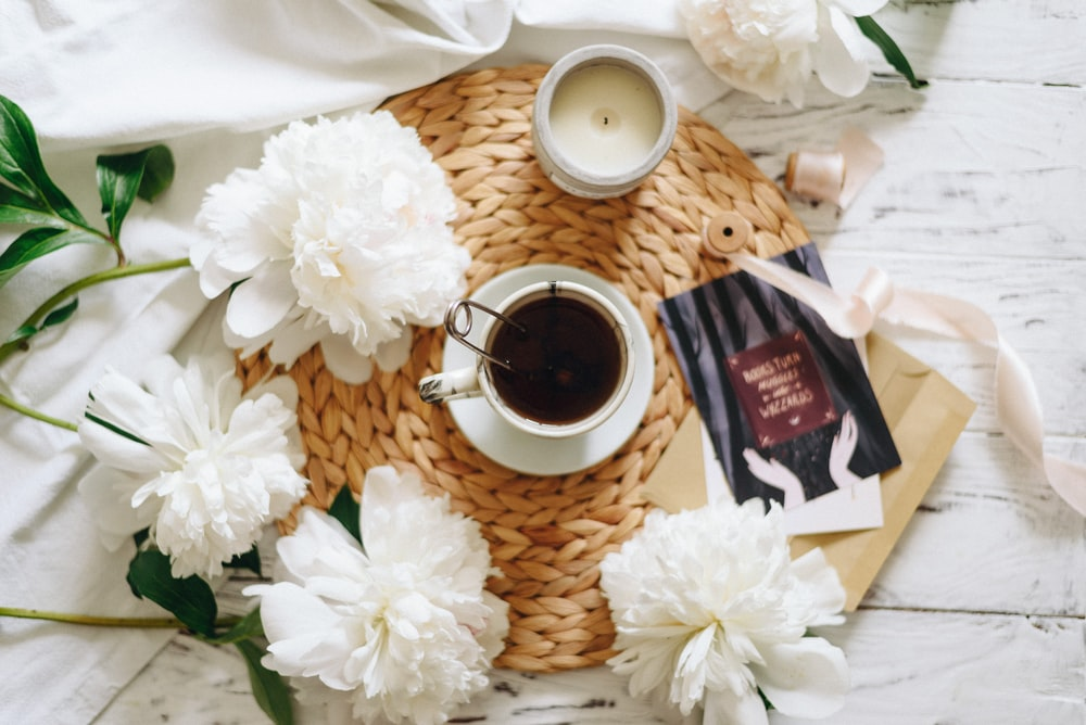 flat lay photography of teacup surrounded by flowers