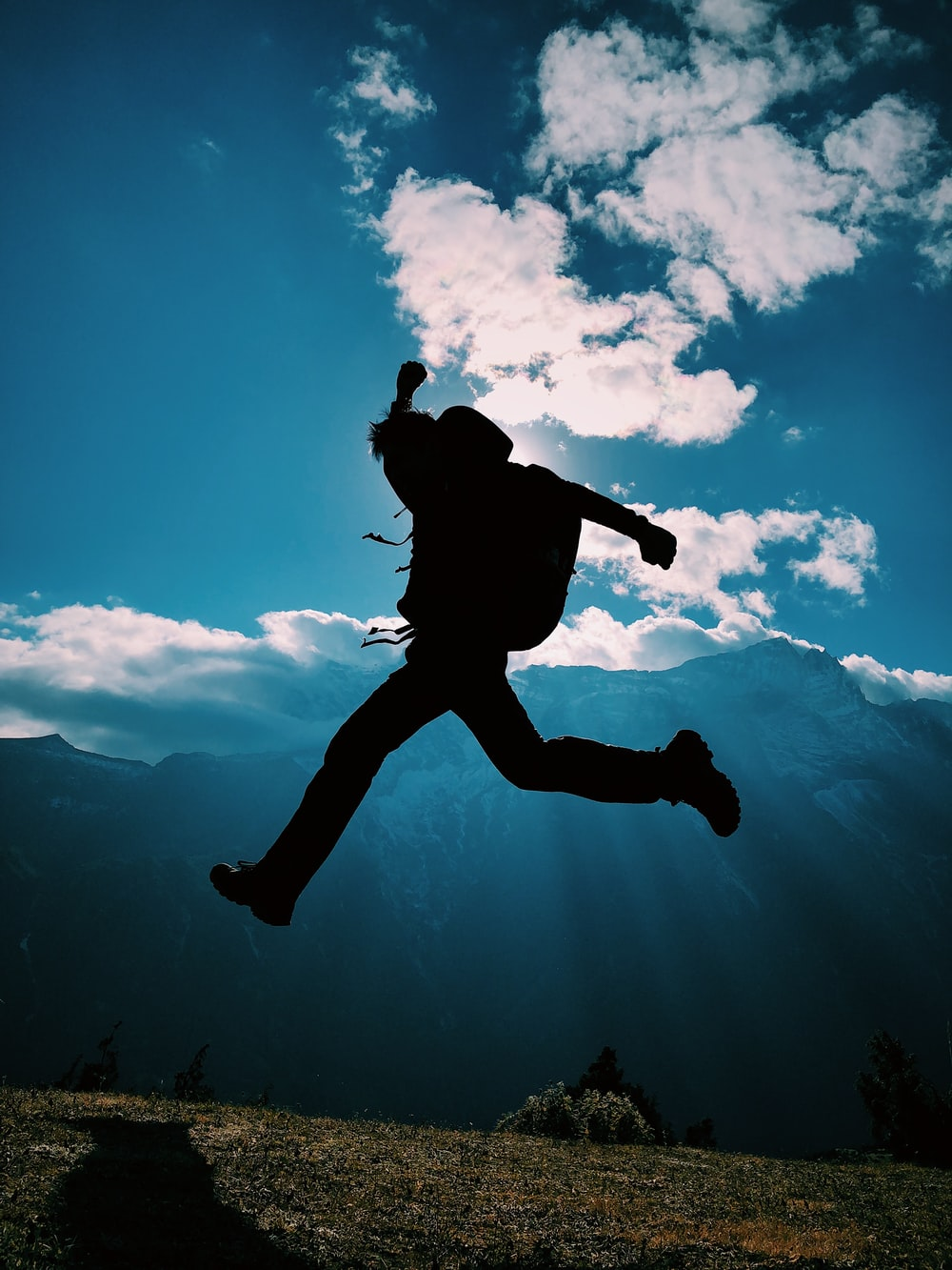 silhouette of person jumping on mountain
