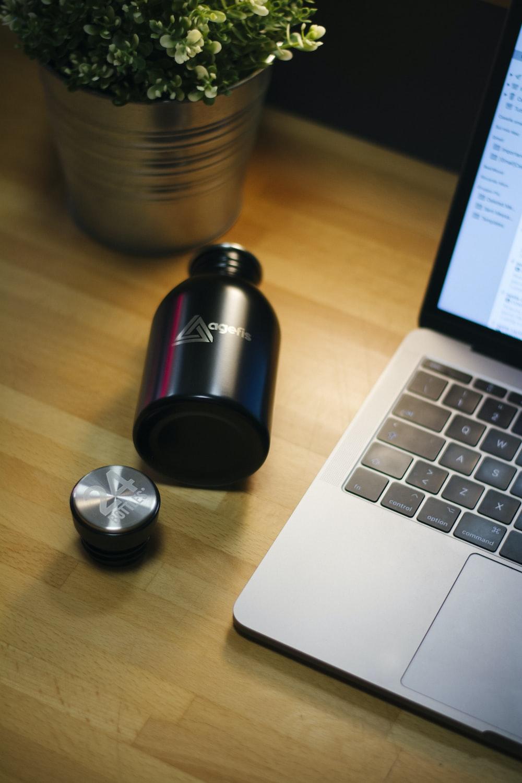 black bottle beside MacBook