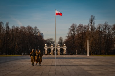 three military soldiers walking at the park near flag pole poland teams background