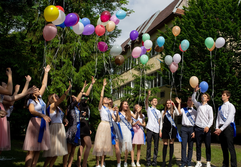 girls and boys flying a balloons