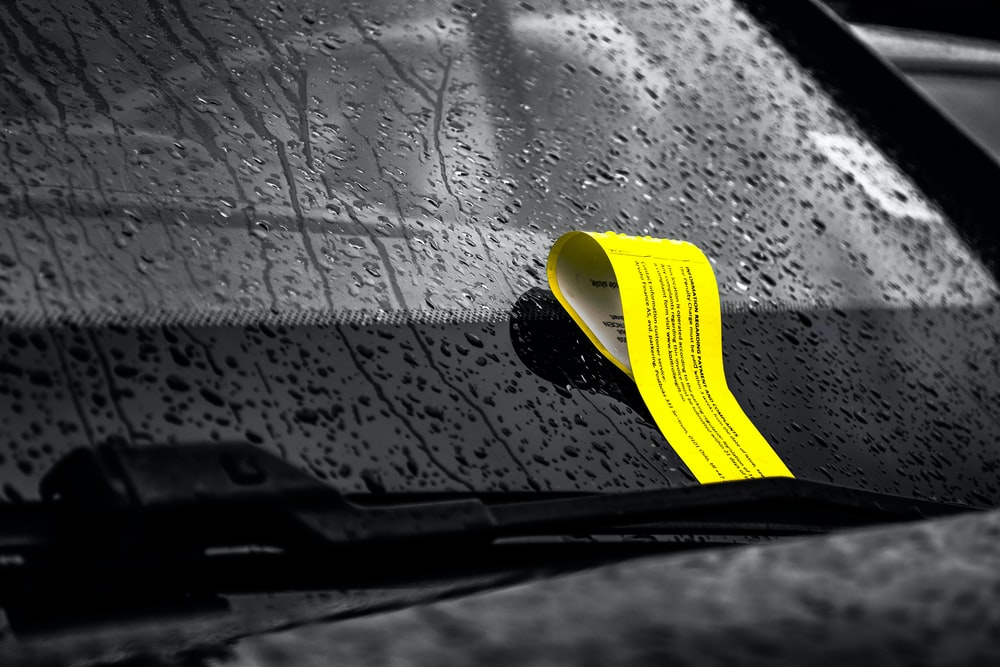 yellow ticket in windshield of vehicle