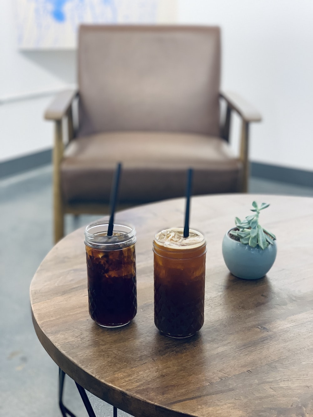 two full-filled jars with straws on table