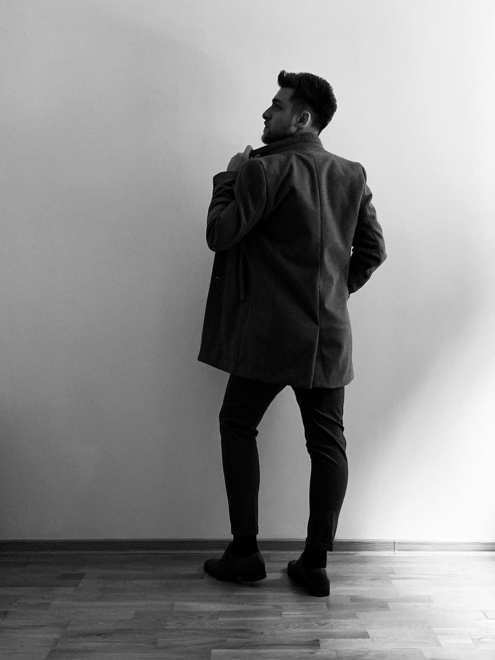man standing beside wall wearing jacket