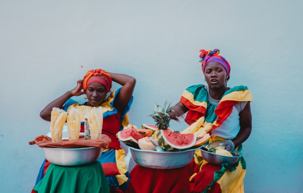 two women sitting beside tubs of foods