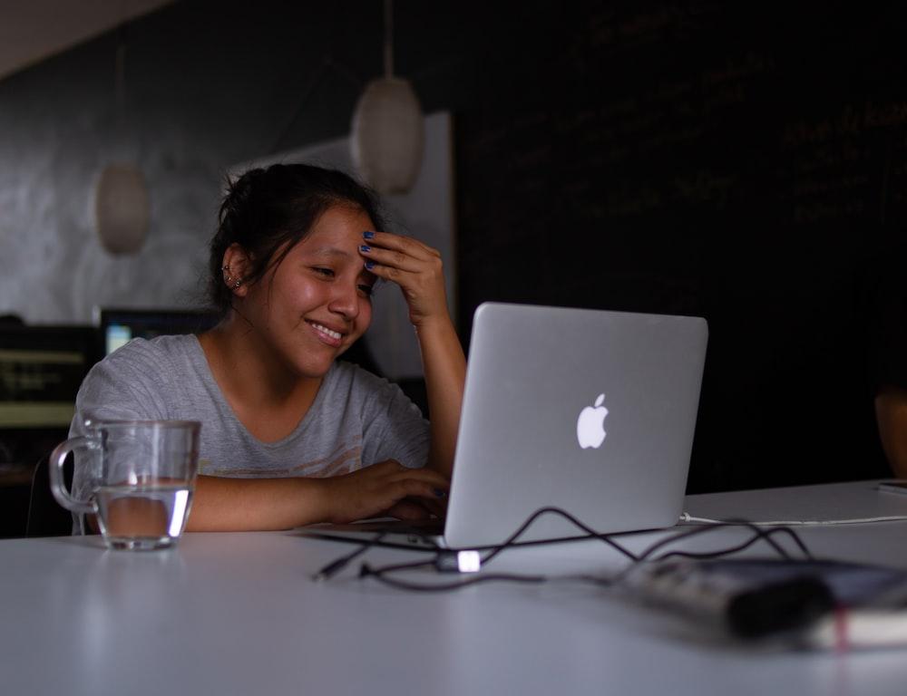 smiling woman using MacBook