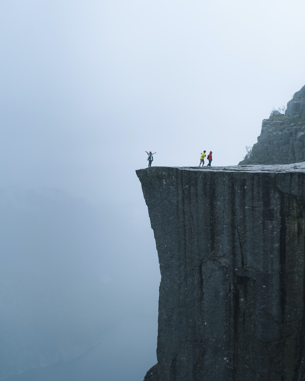 three persons standing near the edge of a cliff during day