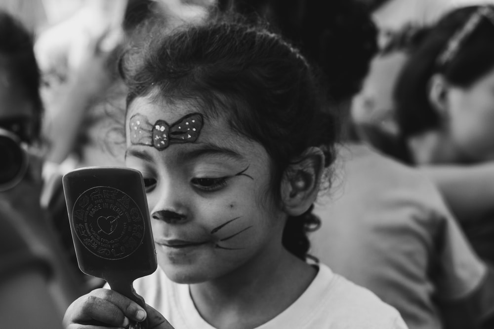 girl with face paint looking at herself on hand mirror