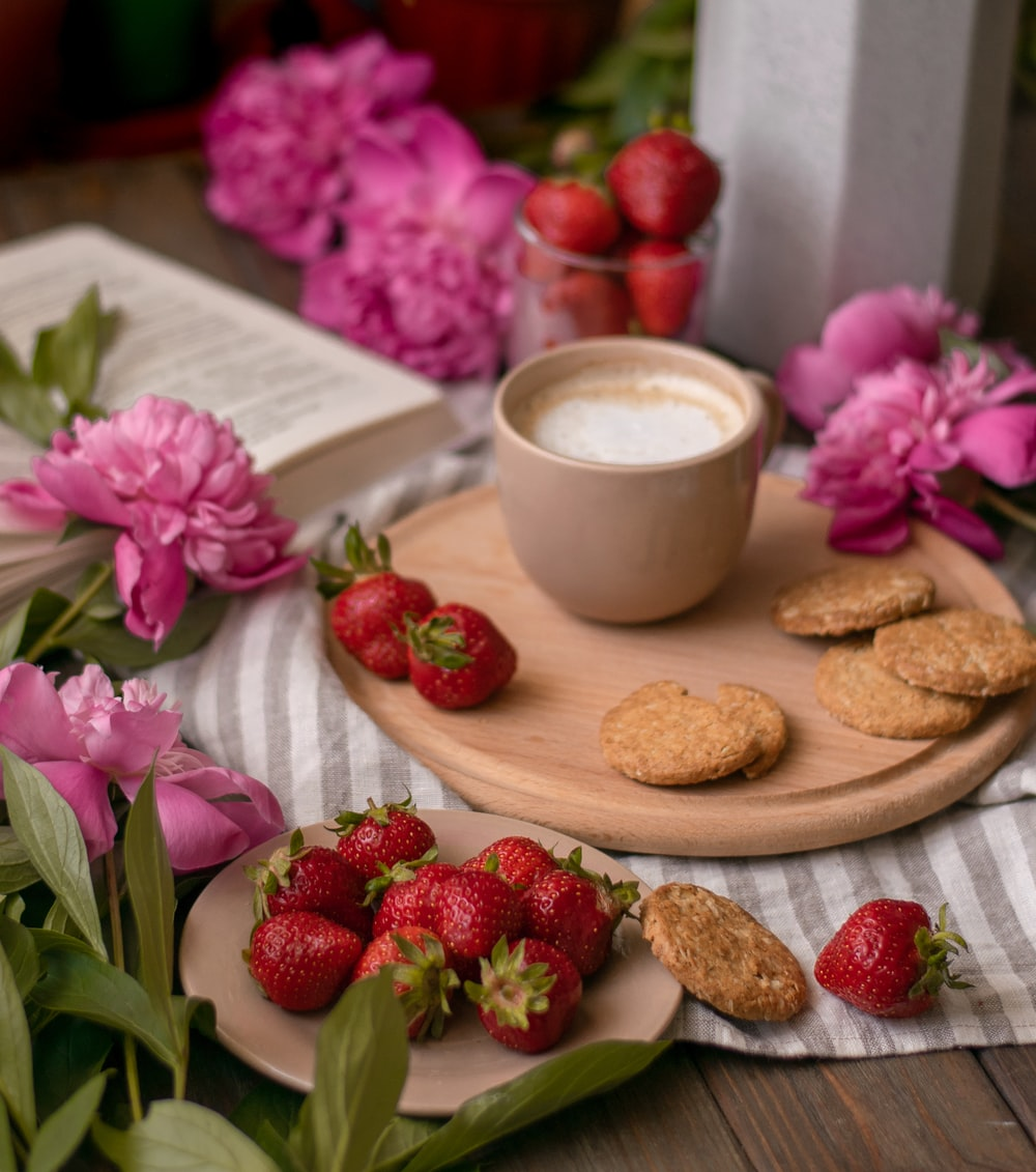 ceramic teacup with latte beside biscuits