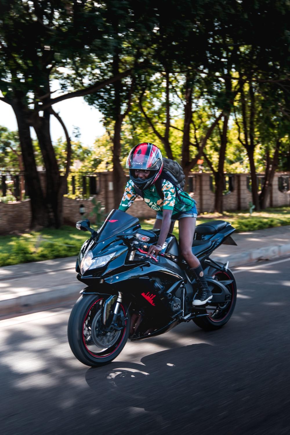 woman on black sport motorcycle in street