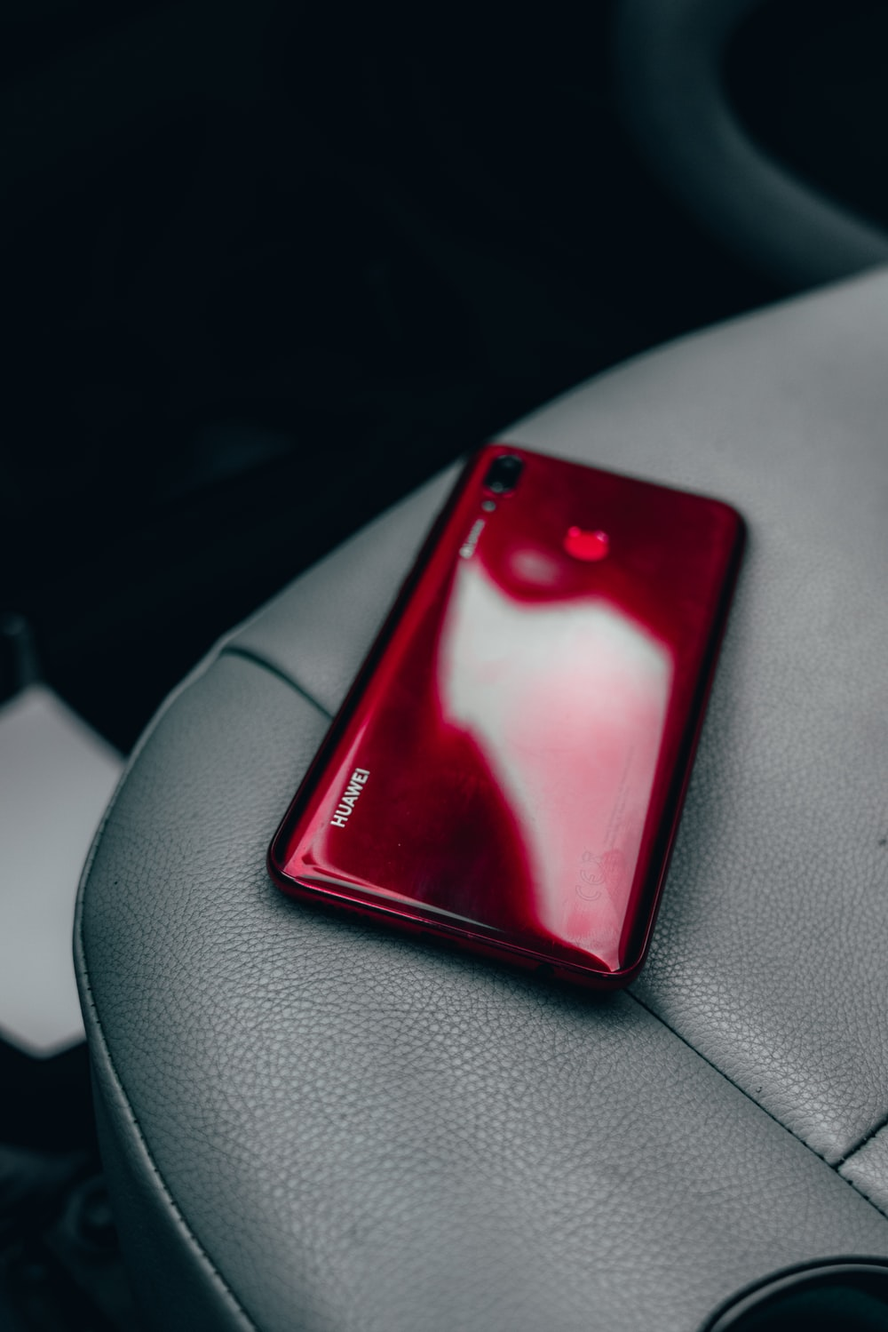 red smartphone on vehicle seat