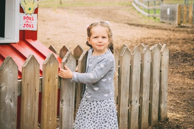 girl standing beside wooden fence