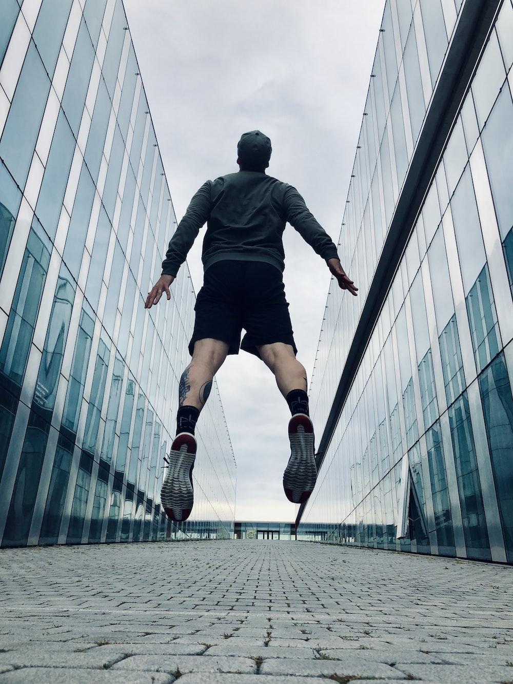 man jumping between high rise building