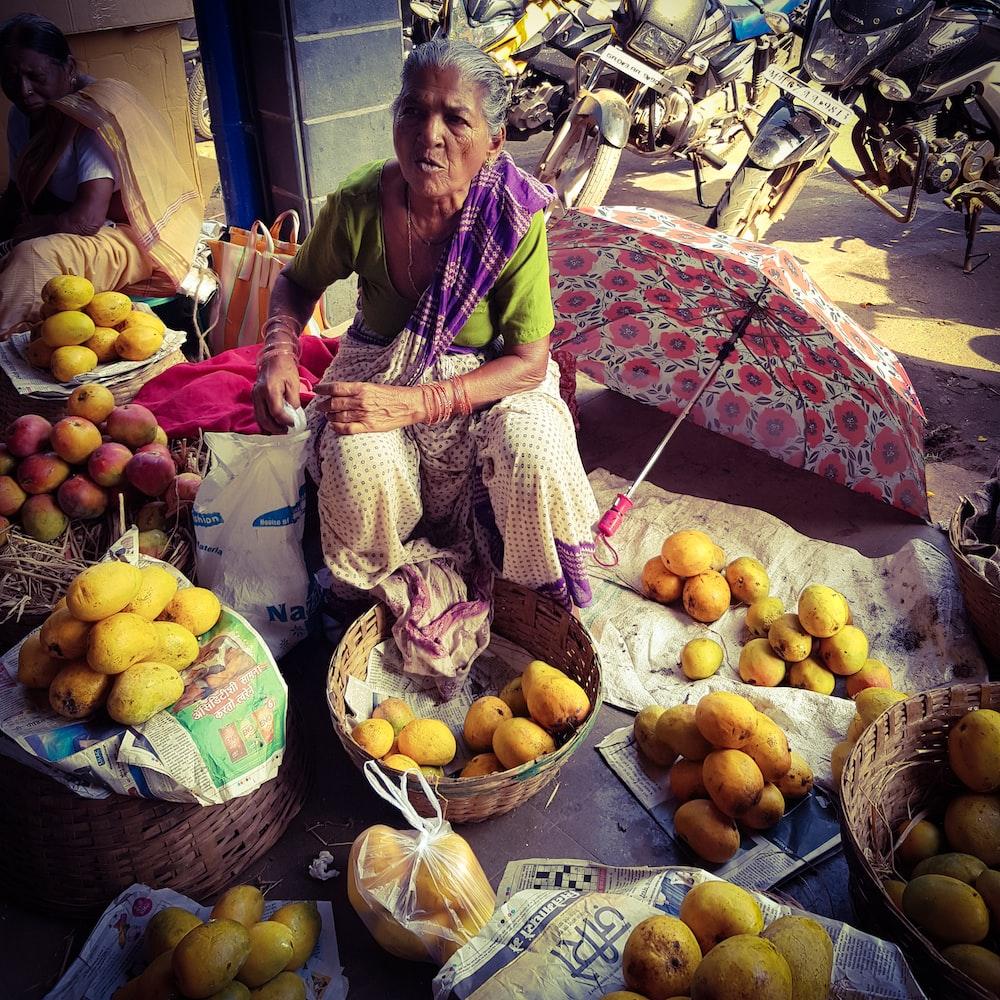 woman in dress sitting near fruits