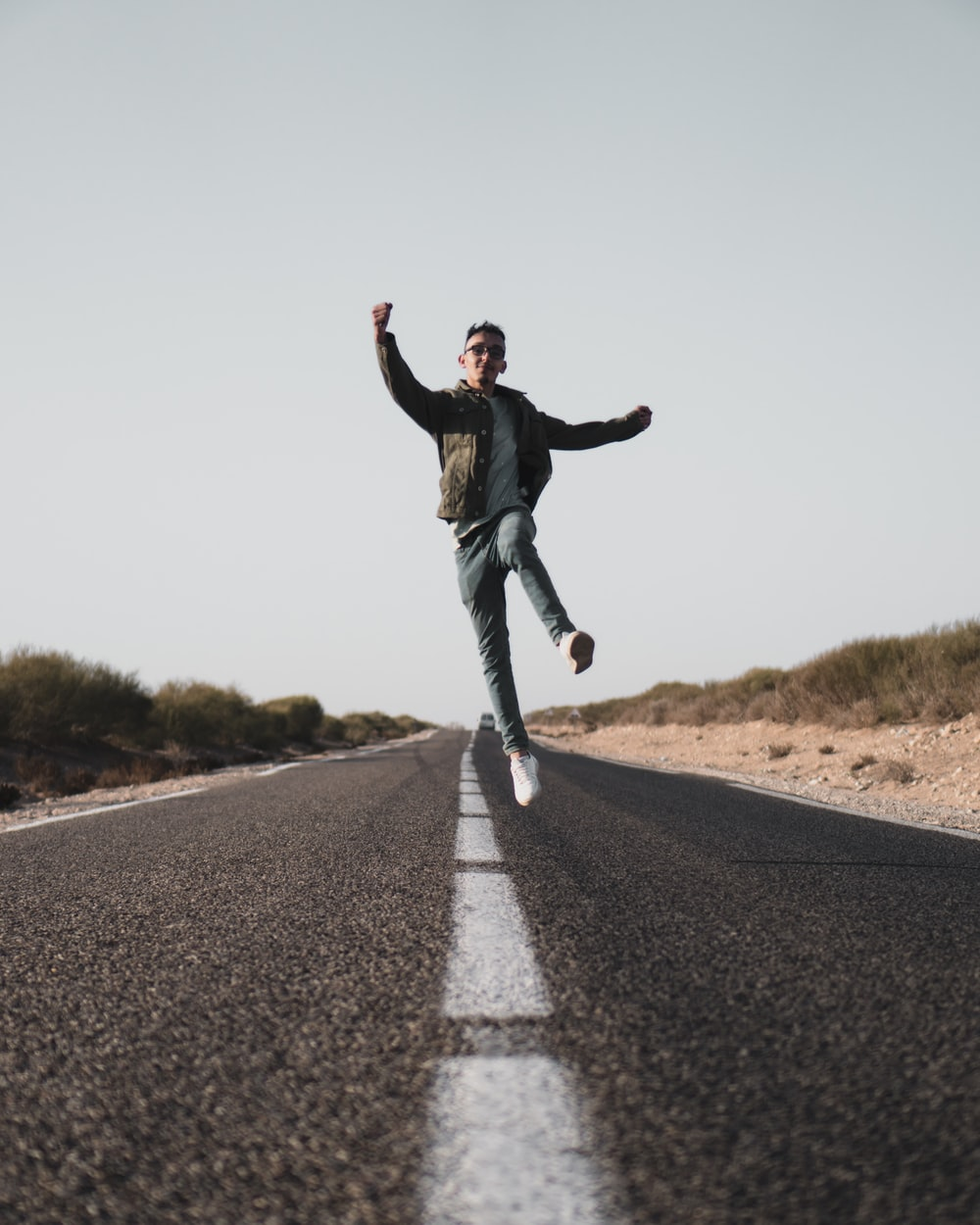 man wearing gray jacket jumping in the middle of asphalt road
