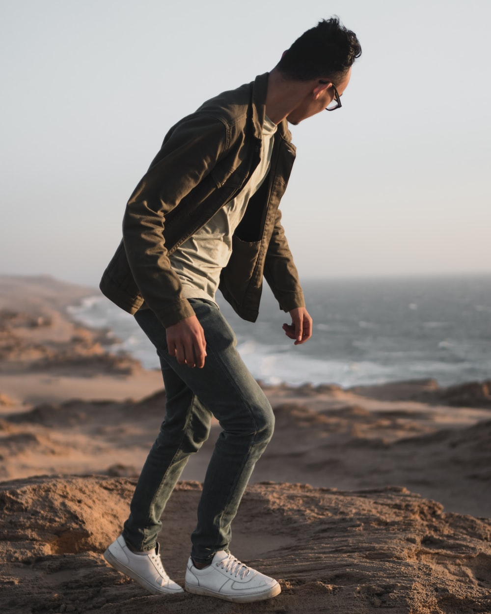 man on a cliff and a beach