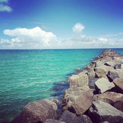 landscape photography of seawall on blue sea