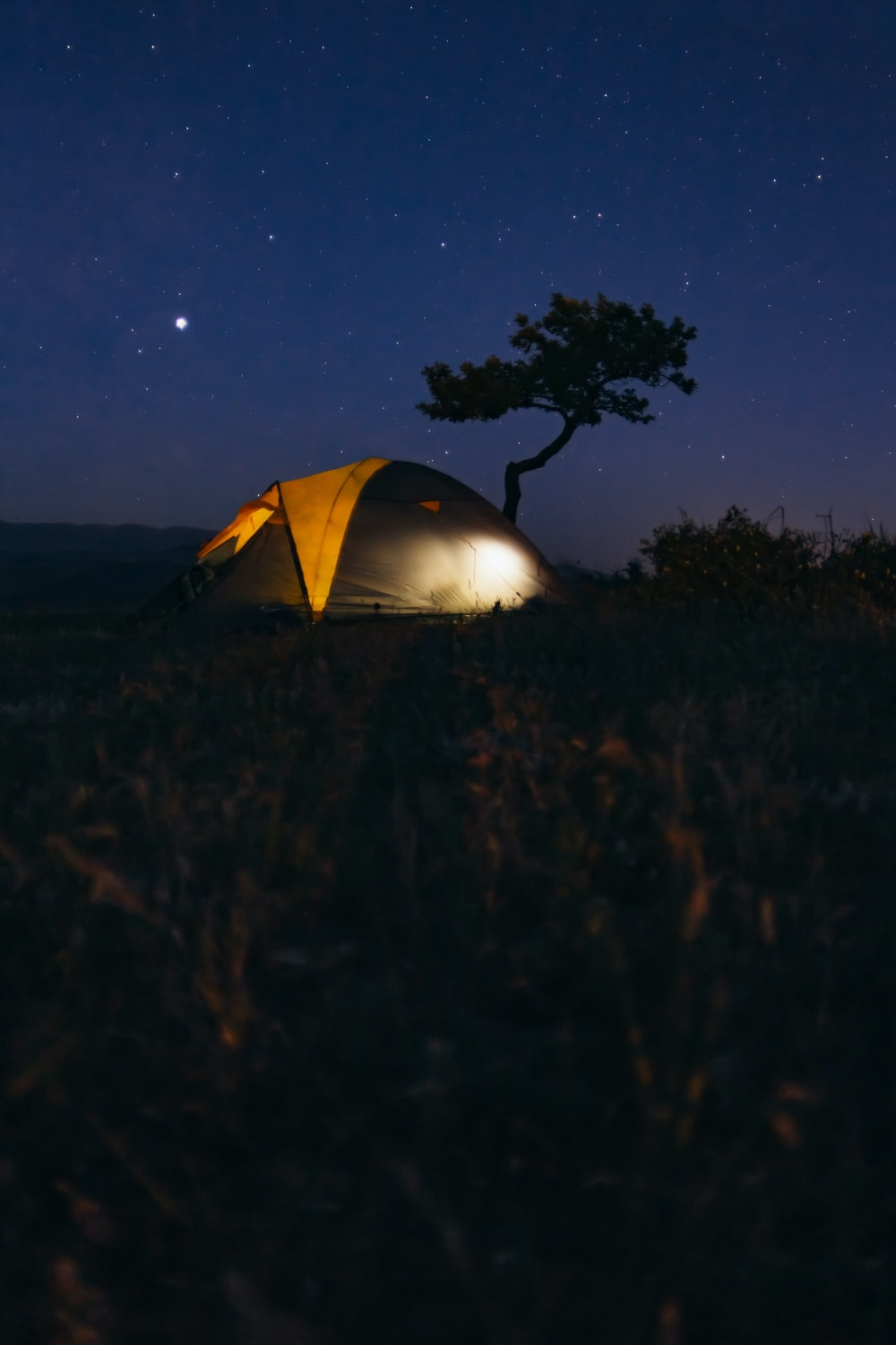 gray and yellow camping tent in the middle of grass field camping during nightime