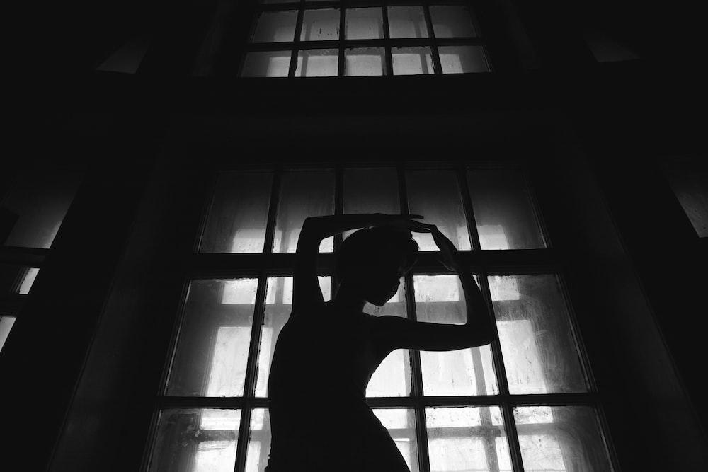 woman dancing behind glass window