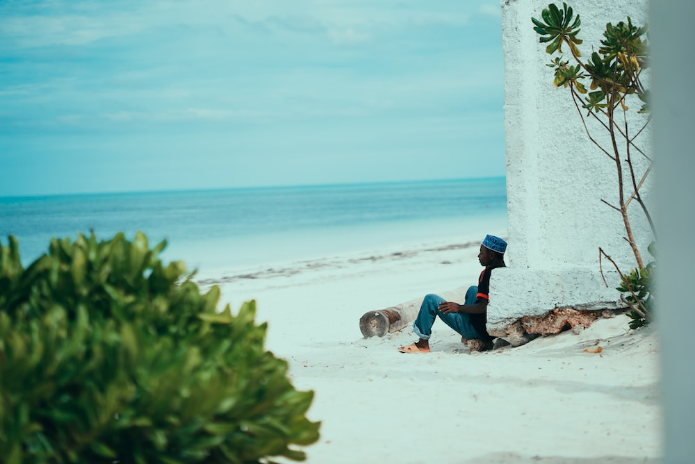 shallow focus photo of person sitting on seashore during daytime