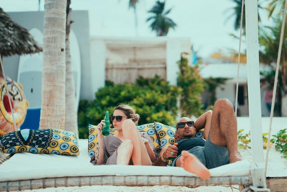 man and woman lying on lounge
