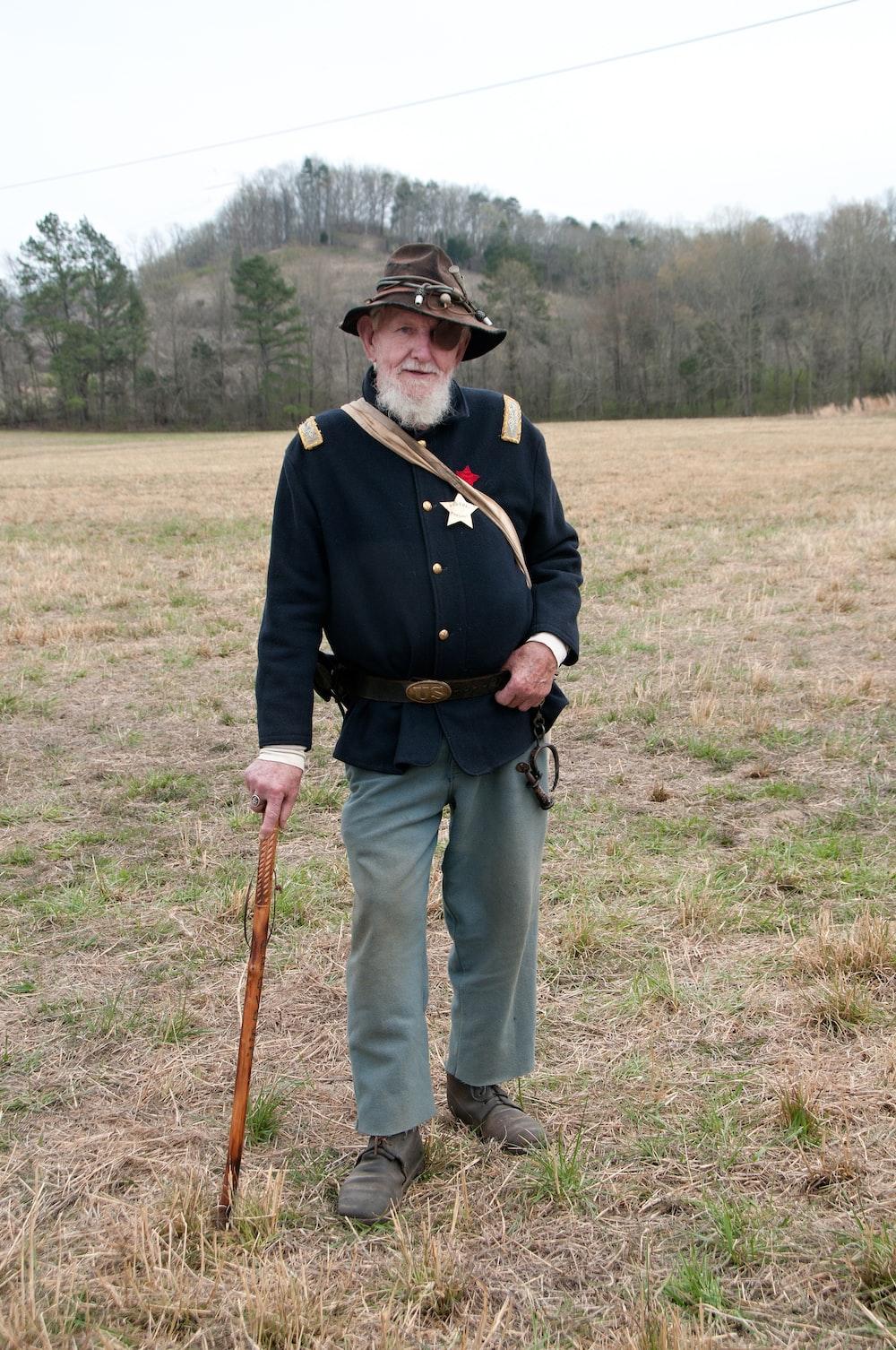 man in black coat standing on grass