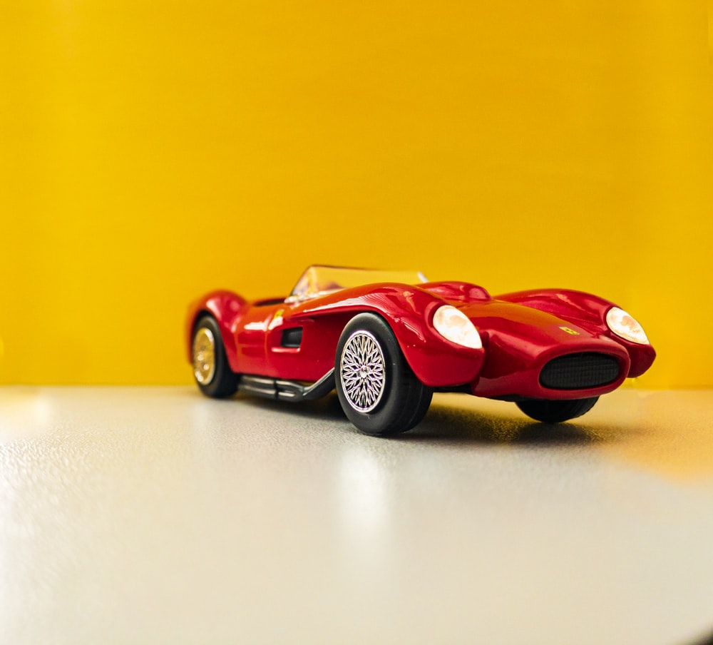 red coupe scale model on white surface