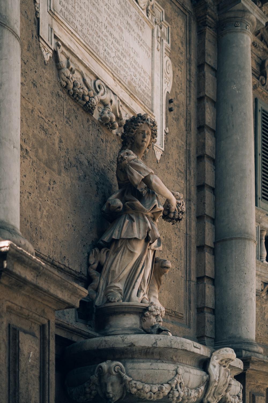 woman sculpture beside wall
