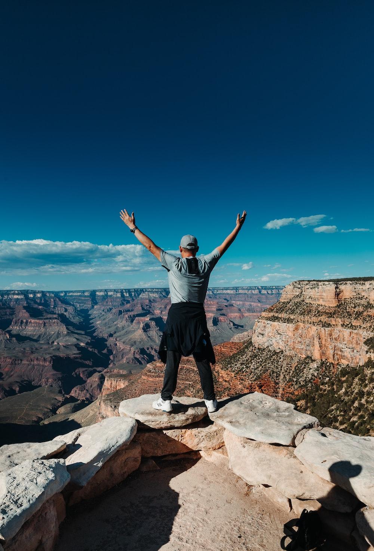 man wearing gray crew-neck shirt standing on mountain edge