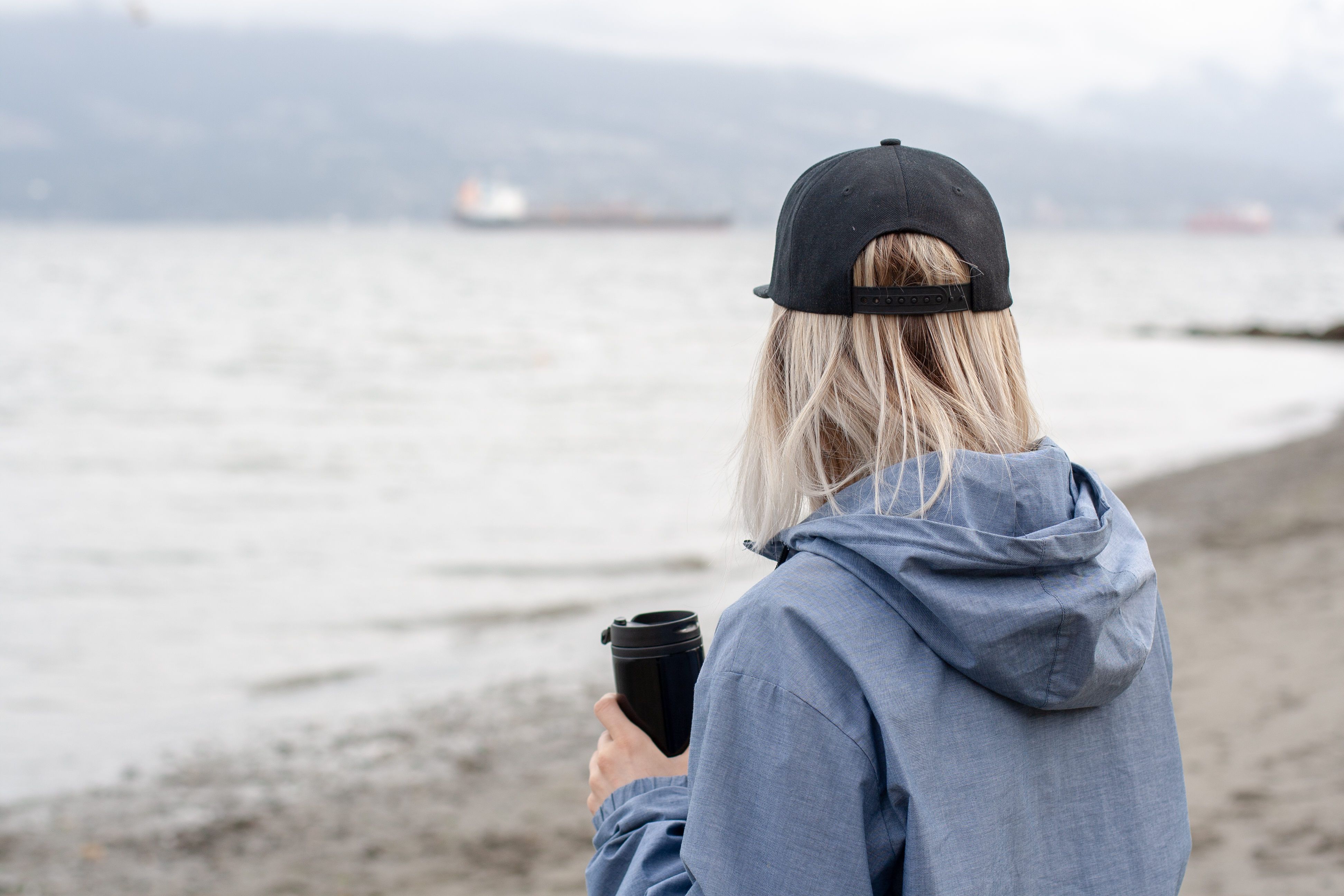 woman standing beside beach while holding black tumbler