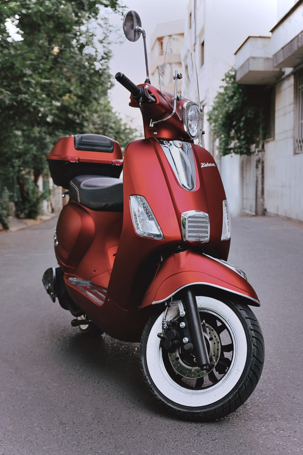 red motor scooter parked near tree and buildings