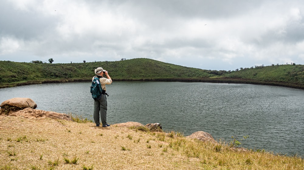 person with backpack standing in front of lake
