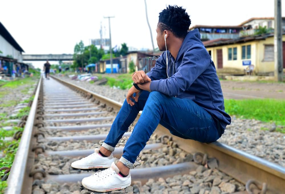 man sitting on rail
