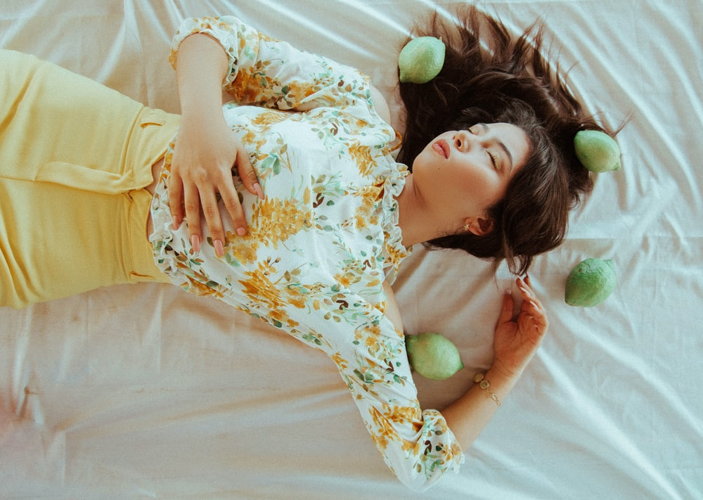 girl lying on fabric surrounded with fruits